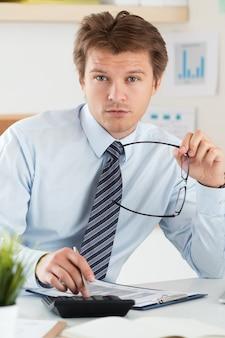 Portret księgowego lub inspektora finansowego trzymającego okulary, sporządzającego raport, obliczającego lub sprawdzającego saldo. finanse domu, inwestycje, gospodarka, oszczędność pieniędzy lub koncepcja ubezpieczenia