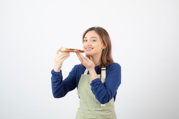 Portret kucharki w fartuchu trzymającej pizzę i uśmiechniętej