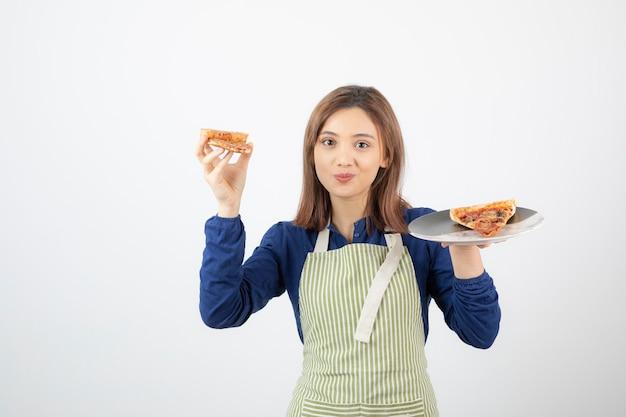Portret kucharki w fartuchu trzymającej pizzę na białym tle