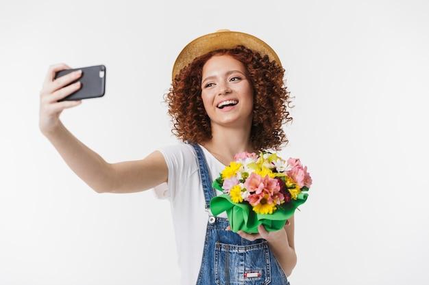 Portret kuszącej rudowłosej kręconej kobiety 20 lat w letnim słomkowym kapeluszu robi zdjęcie selfie, trzymając pudełko z kwiatami izolowane nad białą ścianą
