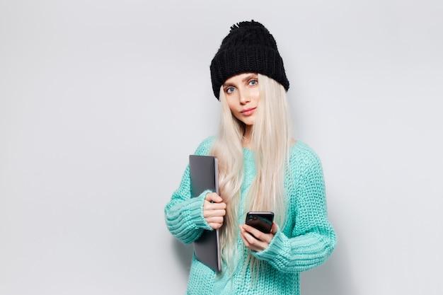 Portret ładna blondynka z laptopem w rękach przy użyciu smartfona