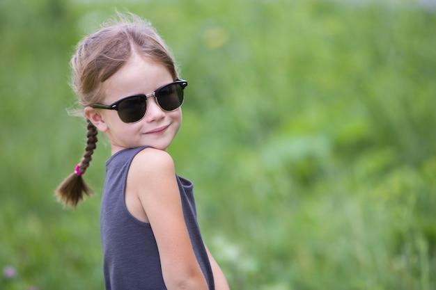 Portret ładna dziecko dziewczyna z warkoczami w włosy outdoors w lecie.