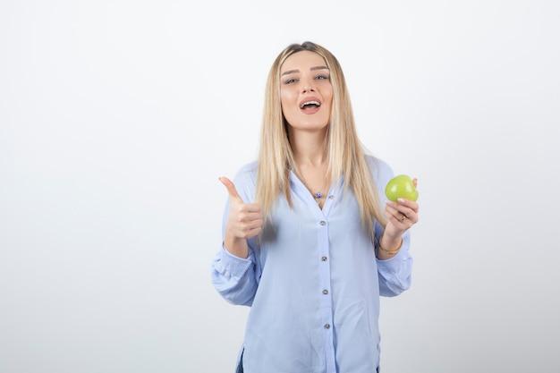 Portret ładna dziewczyna trzyma zielone świeże jabłko i pokazuje kciuk.