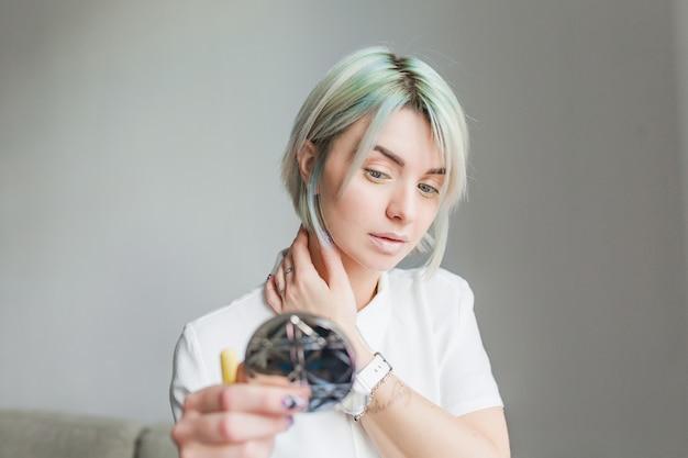 Portret ładna dziewczyna z krótkie szare fryzury na szarym tle. ubrana jest w białą sukienkę i patrzy w lustro w dłoni.