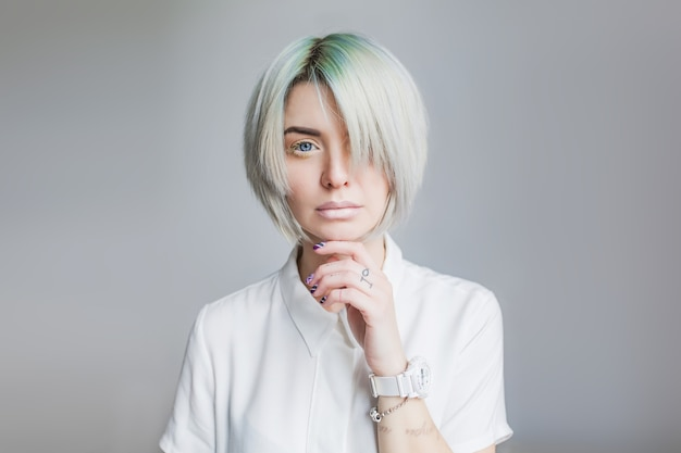 Portret ładna dziewczyna z szarej krótkiej fryzury na szarym tle. nosi białą sukienkę i lekki makijaż. grzywka obejmuje połowę twarzy. jej dłoń dotyka twarzy.