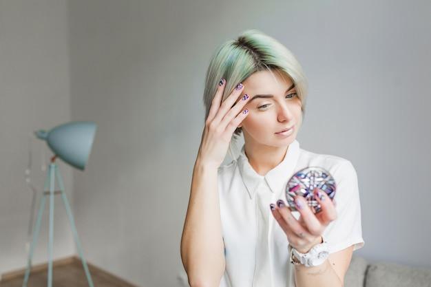 Portret ładna dziewczyna z szarej krótkiej fryzury stojącej w szarym studio. nosi białą sukienkę i lekki makijaż. w rękach trzyma lustro.