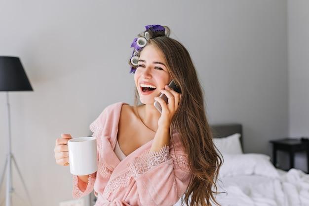Portret ładna gospodyni domowa w różowym szlafroku z lokówką w domu. mówi przez telefon i uśmiecha się.