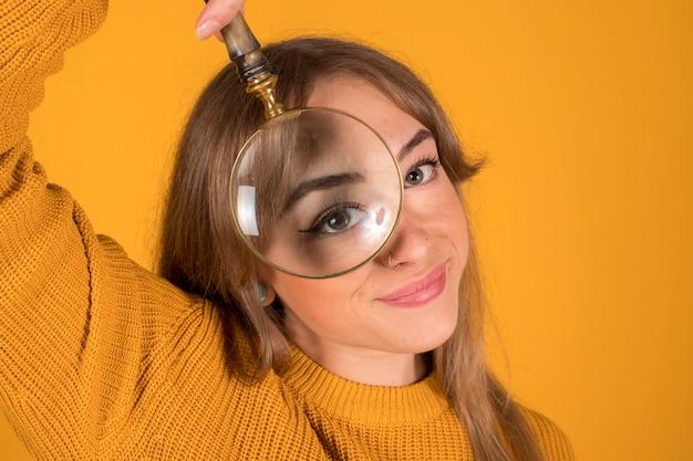 Portret ładna i rozochocona kobieta patrzeje kamerę przez powiększać - szkło