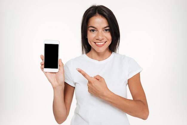 Portret ładna kobieta przedstawia pustego ekranu telefon komórkowego