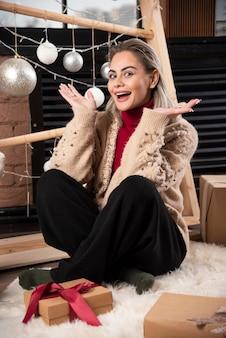 Portret ładna kobieta siedzi z prezentami świątecznymi