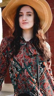 Portret ładna kobieta ubrana w sukienkę i słomkowy kapelusz w dzień słoneczny i pogodny. chodzenie w letnim parku.