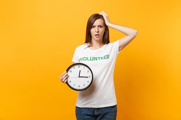 Portret ładna kobieta w białej koszulce z napisem zielony tytuł wolontariusz trzymać okrągły zegar na białym tle na żółtym tle. dobrowolna bezpłatna pomoc, koncepcja czasu pracy charytatywnej łaski