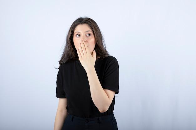Portret ładna kobieta w czarnym stroju, patrząc na zakrywając usta.