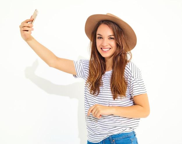 Portret ładna kobieta w lato modnisiu odziewa brać selfie odizolowywającego na biel ścianie