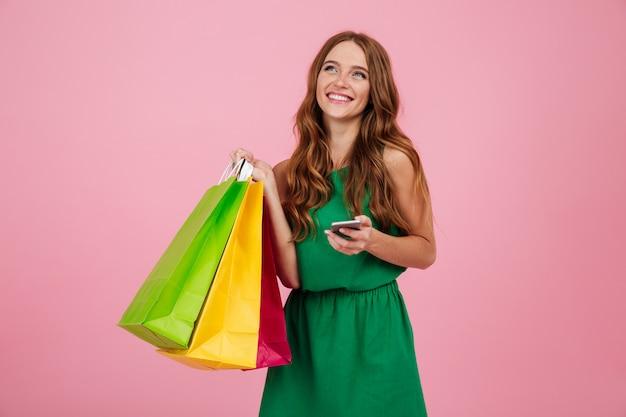 Portret ładna kobieta w sukni posiadania telefonu komórkowego