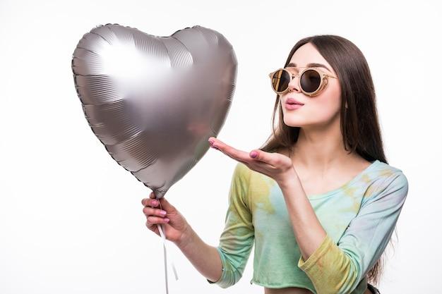Portret ładna kobieta wysyła pocałunek powietrza w kształcie serca czerwony balon