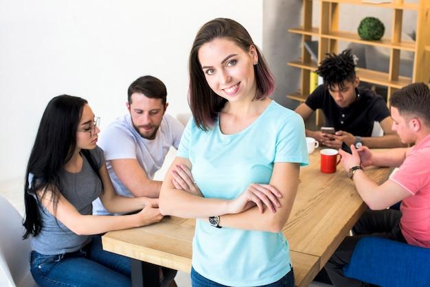 Portret ładna kobieta z ręką krzyżował pozycję z jej przyjaciółmi siedzi behind