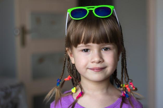 Portret ładna mała dziewczynka z małymi warkoczami