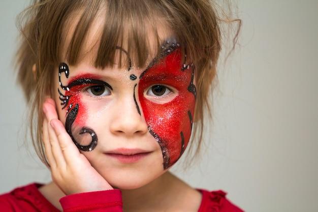Portret ładna mała dziewczynka z motylim obrazem na jej twarzy