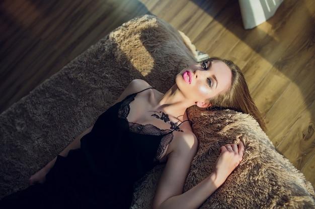 Portret ładna młoda dziewczyna na łóżku w nowożytnym mieszkaniu w ranku