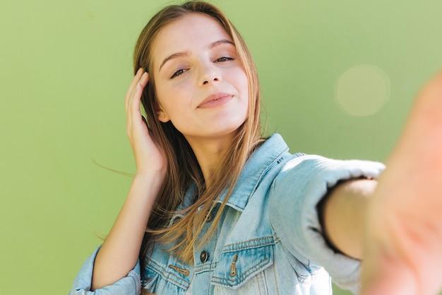 Portret ładna młoda kobieta bierze jaźń portret na zielonym tle