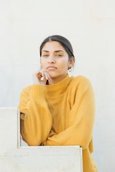 Portret ładna młoda kobieta patrząc na kamery opierając się na schodach