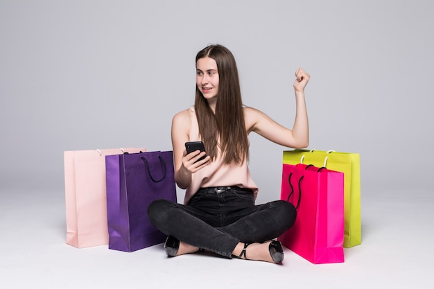 Portret ładna młoda kobieta siedzi na podłodze z torby na zakupy i używa telefonu komórkowego z wygranym gestem nad szarości ścianą