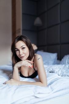 Portret ładna młoda kobieta w łóżku wczesnym rankiem