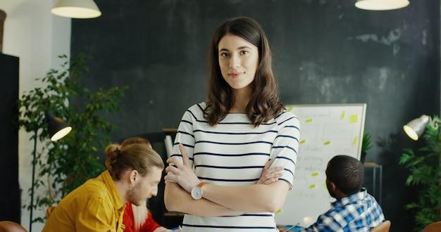 Portret ładna młoda rozochocona dziewczyna obraca twarz w kamerę i ono uśmiecha się. drużyna startupów na tle.