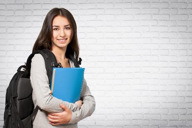 Portret ładna młoda studentka trzymająca książkę, na białym tle na tle