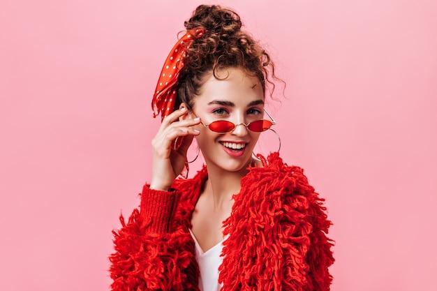 Portret ładna pani w czerwonej ciepłej kurtce i stylowych okularach