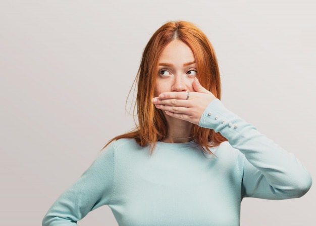 Portret ładna rudzielec dziewczyna zakrywa jej usta
