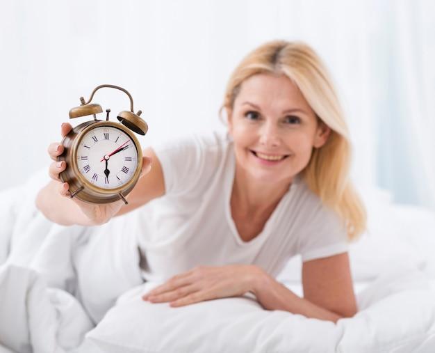 Portret ładna starsza kobieta trzyma alarm