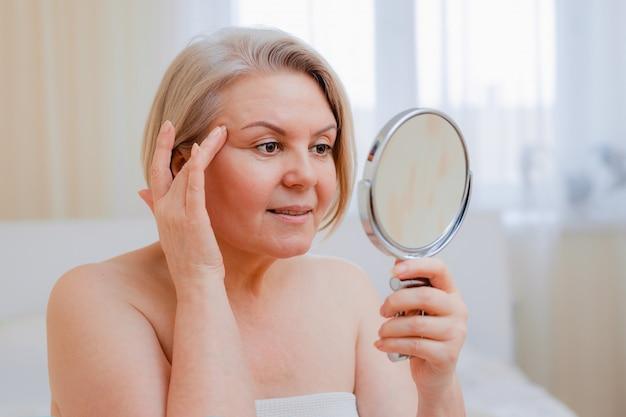 Portret ładna starsza kobieta z rękami na jej twarzy lustrze w domu po łazienki