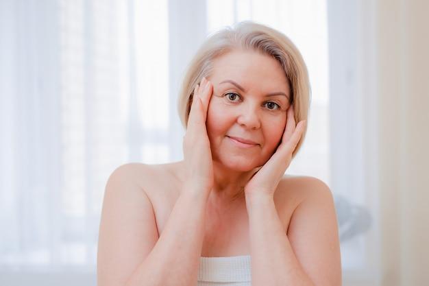 Portret ładna starsza kobieta z rękami na ona twarz