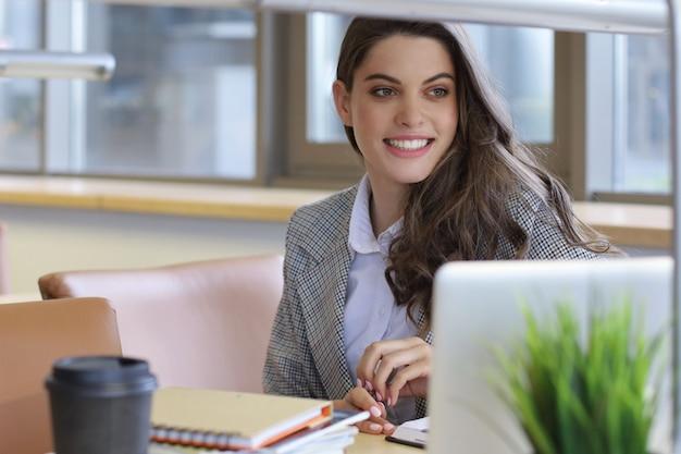 Portret ładna studentka z laptopem w bibliotece.