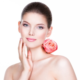 Portret ładna twarz pięknej kobiety z różową różą - na białym tle.