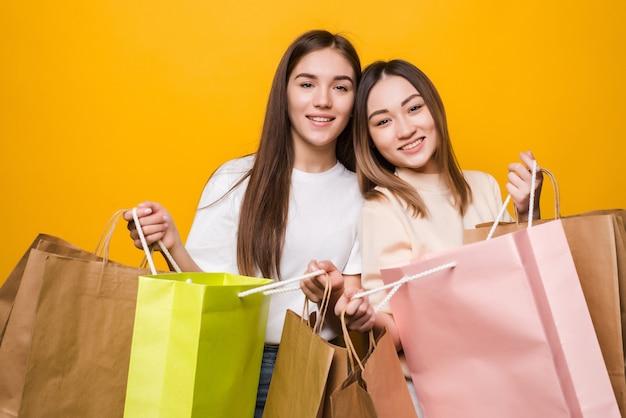 Portret ładne atrakcyjne ładne dziewczyny niosące kolorowe torby zabawy na białym tle na żółtej ścianie