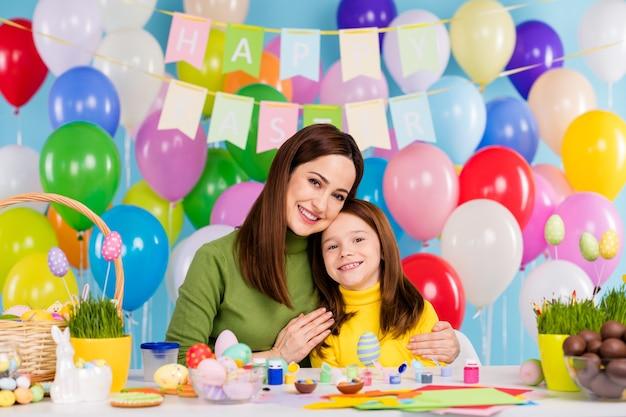 Portret ładne atrakcyjne, urocze, delikatne wesołe dziewczyny, przygotowujące rękodzieło ręcznie robione czekoladowe jajka obejmujące małą, czerwonowłosą siostrę