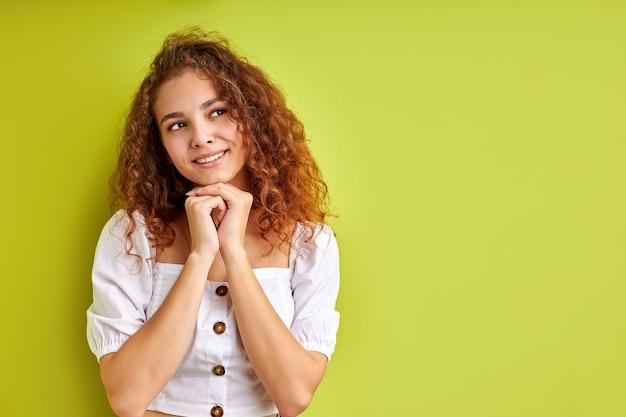 Portret ładne całkiem marzycielski kręcone dziewczyna myśli fantazjując na białym tle na zielonym tle