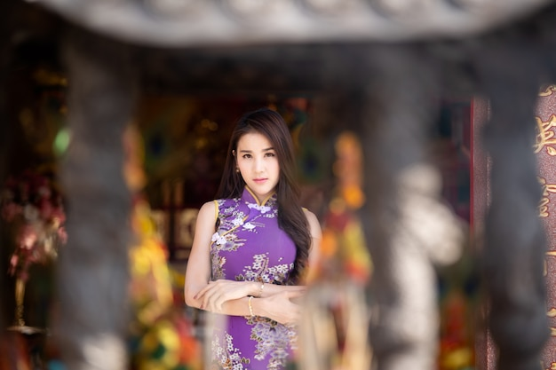 Portret ładne kobiety jest ubranym cheongsam przy plenerowym w asia, chiński dziewczyny pojęcie.