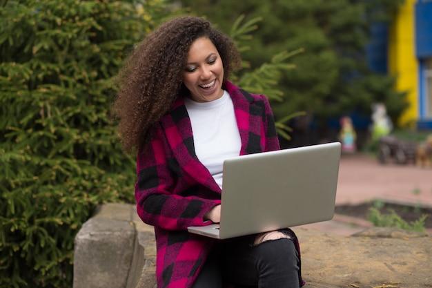 Portret ładne kręcone włosy brunetka dziewczyna z laptopa siedząc na ławce na zewnątrz