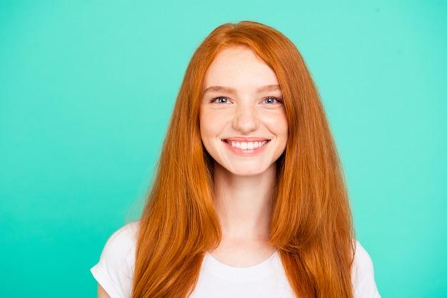 Portret ładne rude dziewczyny na białym tle nad turkusową ścianą
