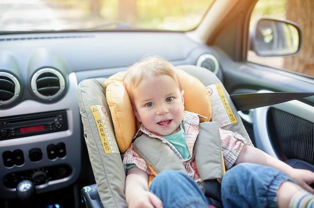Portret ładnego 1-letniego chłopca siedzącego w foteliku samochodowym zamontowanym na przednim siedzeniu.