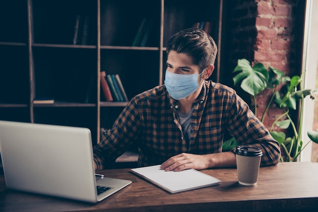Portret ładnego, atrakcyjnego, zajętego, skoncentrowanego faceta noszącego maskę bezpieczeństwa ncov mers ncov zapobieganie zapaleniu płuc utrzymywanie dystansu społecznego na poddaszu cegła przemysłowa stacja robocza w pomieszczeniu