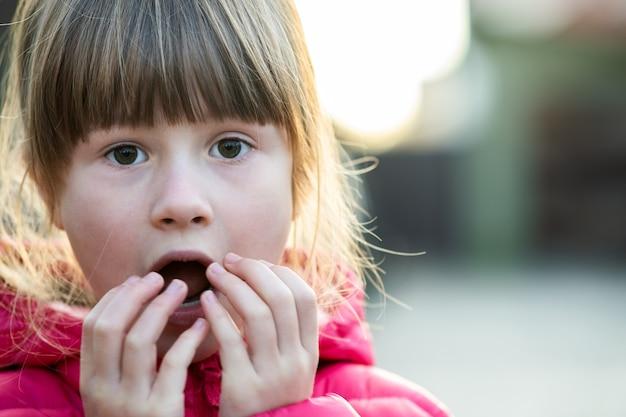 Portret ładnego dziecka dziewczyna robi zadziwiającemu drżącemu wyrażeniu na jej twarzy outdoors.