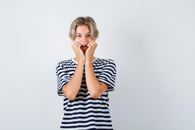 Portret ładnego nastoletniego chłopca opierającego policzki na rękach w pasiastym t-shircie i patrzącego wesoło na widok z przodu