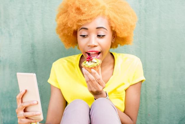 Portret ładnej afrykańskiej kobiety w żółtej koszulce, która robi zdjęcie selfie ze słodkim deserem na zielonym tle