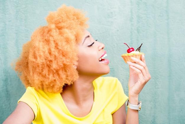 Portret ładnej afrykańskiej kobiety w żółtej koszulce trzymającej słodki deser z wiśnią na zielonym tle