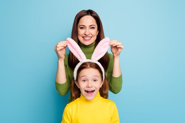 Portret ładnej atrakcyjnej uroczej zabawnej uroczej całkiem wesołej wesołej dziewczyny mama dotykająca uszy królika córki, zabawy na białym tle nad jasnym, żywym połyskiem, żywym niebieskim kolorem